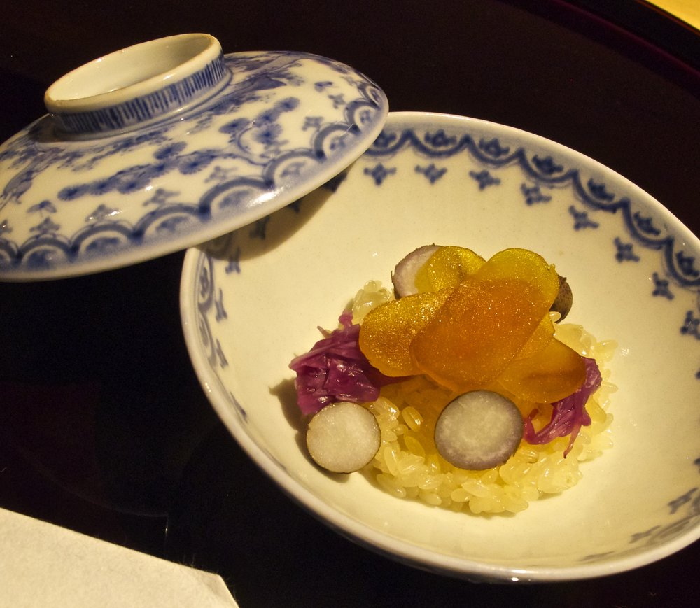 Sakizuke (先附) - The first course is a kind of amuse-bouche. In this case it is a beautifully composed small bowl of sticky rice topped with slices of bottarga (cured fish roe), tiny chunks of mukago tubers, and pickled purple chrysanthemum leaves, which are the seasonings and flavorings. It is an appetizing conceit of an entire meal of fish, rice, vegetable, and pickles in one dish. The home-made bottarga is exceptionally mild, luscious, and creamy because Shigeru not only salts the fish roe but also preserves it in shochu liquor for one year.