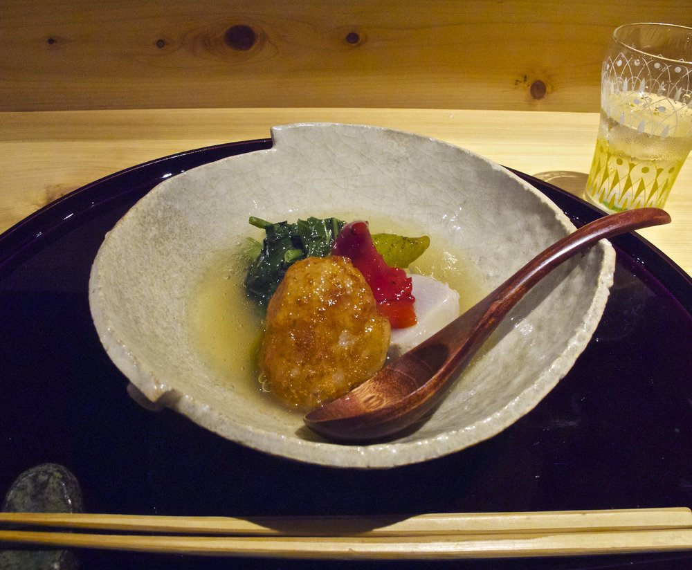 Shiizakana (強肴) - This is a substantial dish in which Shigeru has showcased a variety of tubers (imo in Japanese) and roots. The centerpiece is a paste made of ground Kaga renkon lotus roots and very white, sticky and fine-grained yamato-imo potato that has been rolled into balls and double-fried to heighten their richness as well as give them a lovely crispy crust and light fluffy interior. This is served with a piece of boiled sato-imo taro on the side and topped with bright red and spicy manganji togarashi pepper, light and refreshing kushinsai water spinach, and bitter and crisp saru-togan winter melon slices.