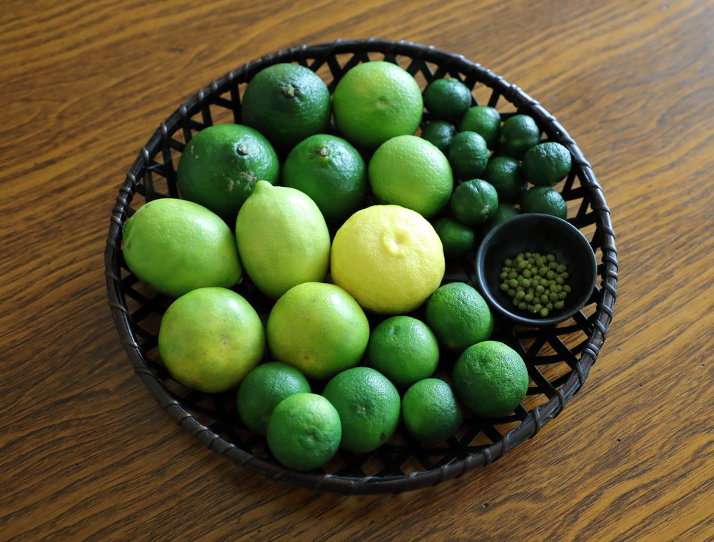 A basket of seasoning citrus in many delightful shades of green during their peak season of autumn. Only  yuzu  at center is served when it ripens to yellow in winter because the fruit is believed to convey the sense of warmer weather. Going clockwise from the small  sansho  berries in a cup on the right are a handful of golfball-sized  sudachi , two larger round  aomikan , two green lemons, three  yuzu kichi , two  kabosu , and and a pile of small dark green  shikwasa .