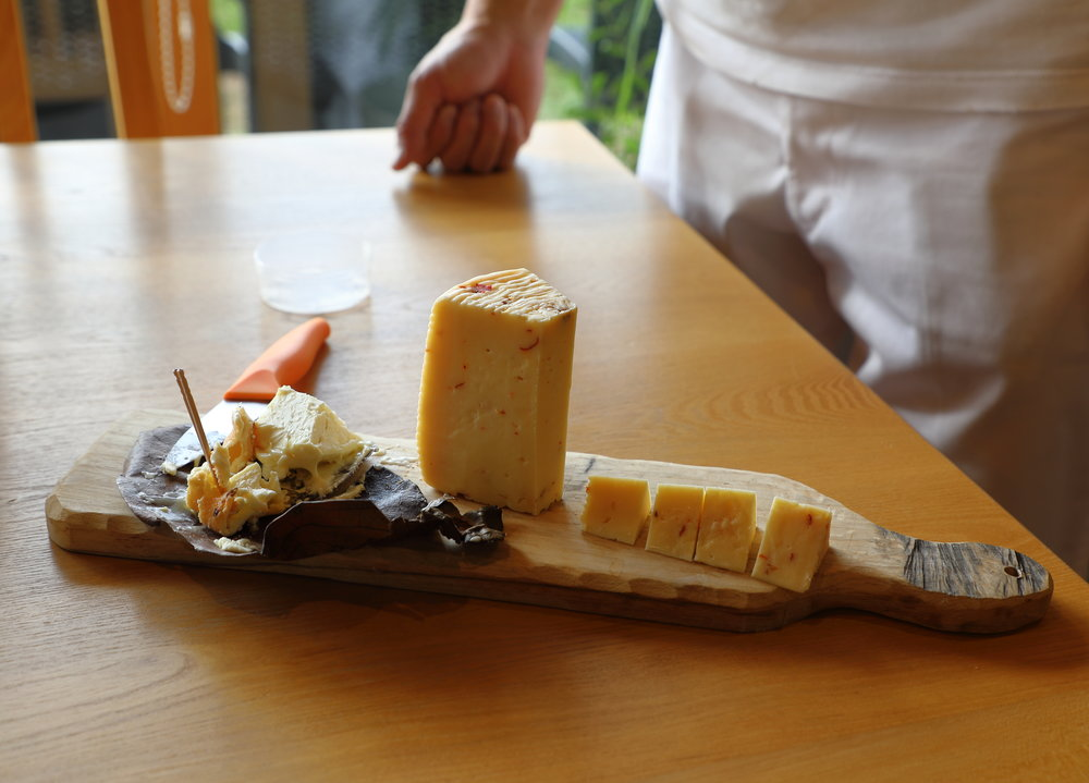 """On the left is Mirasaka Fromage's autumnal soft-ripened goat cheese """"Jyukushi-gaki."""" On the right is an aged farmhouse style of cow cheese spiked with flecks of spicy  togarashi  pepper. It is a delicious balance of milky, nutty, earthy flavors and crumbly, creamy texture."""