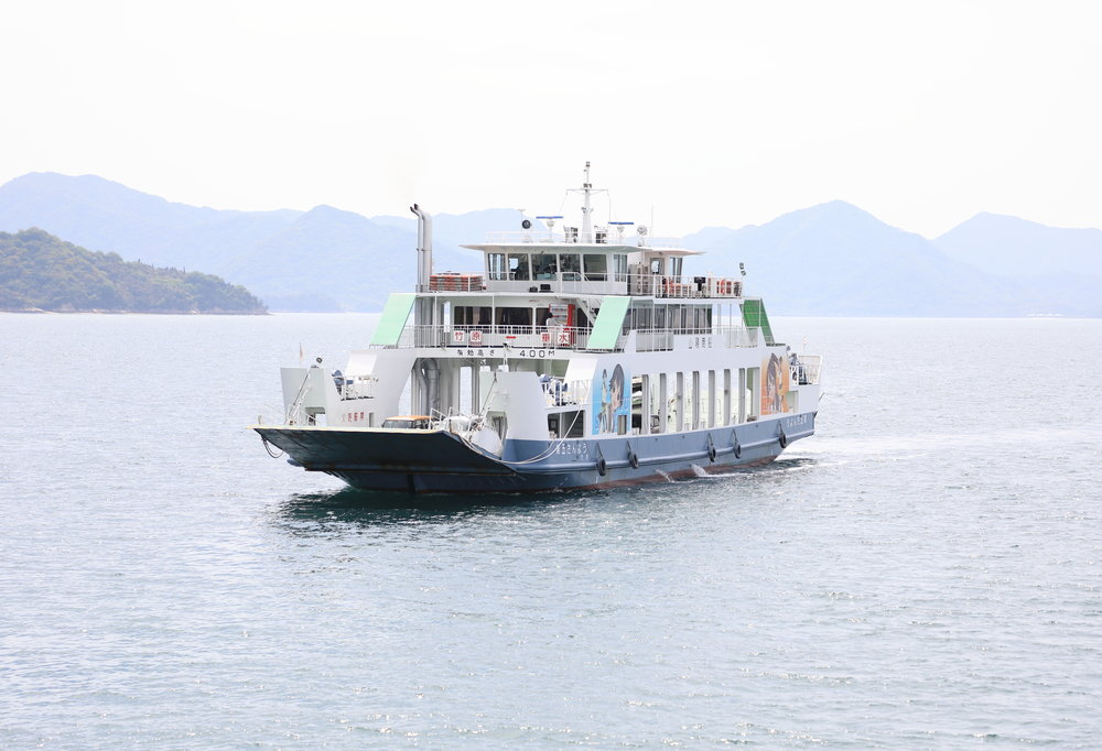 A ferry from the city of Takehara on the mainland Honshu Island traveling to the port of Tarumi on Osakikamijima.