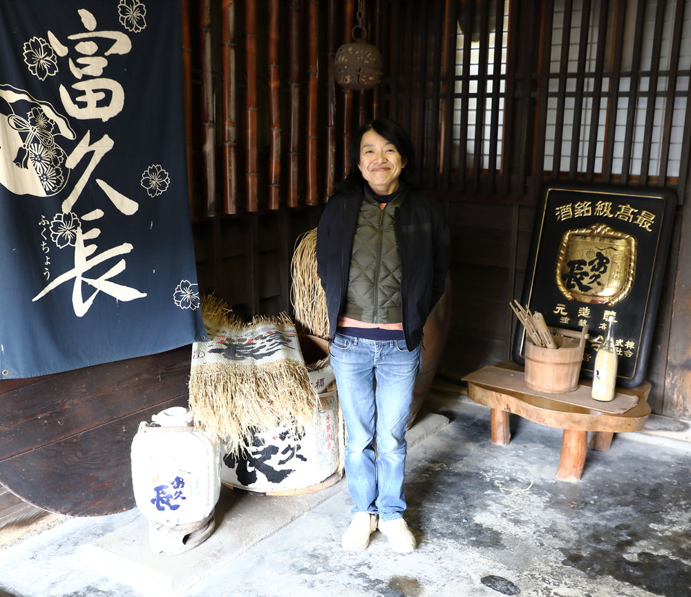 "Miho Imada inside the formal entrance to the sake brewery.  The blue cloth banner hanging to her left is printed with her sake's brand  name and logo of ""Fukucho,"" which means ""Forever Fortune."""