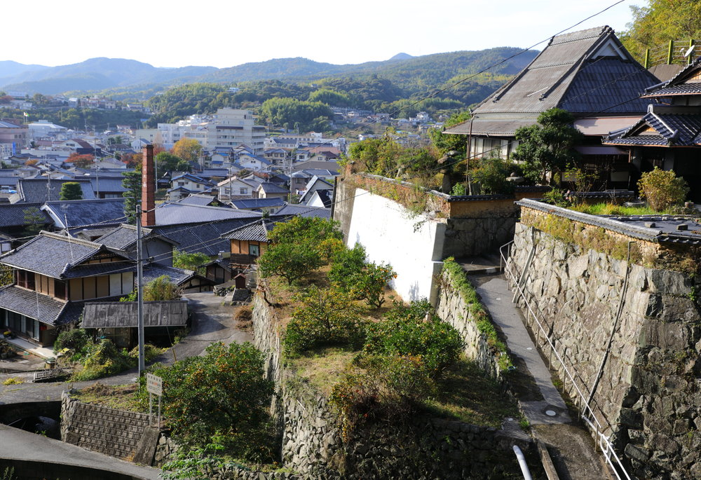 Solemnly overlooking the village of Akitsu, Senzaburo Miura's former house on the right is perched on the top of a series of  ishizumi  stone terraces that are planted with citrus trees and bordered by a narrow mountain stream. Directly below is Imada Shuzo , which is distinguished by its red brick chimney.