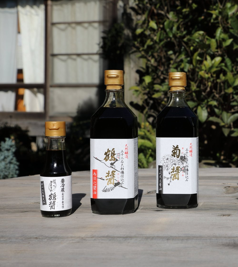 "From left to right: a small bottle of    ki-age  unpasteurized ""Tsuru-bishio""  saishikomi  soy sauce, large bottle of pasteurized  ""Tsuru-bishio""  soy sauce, and a large bottle of ""Kiku-bishio""  koikuch i soy sauce."
