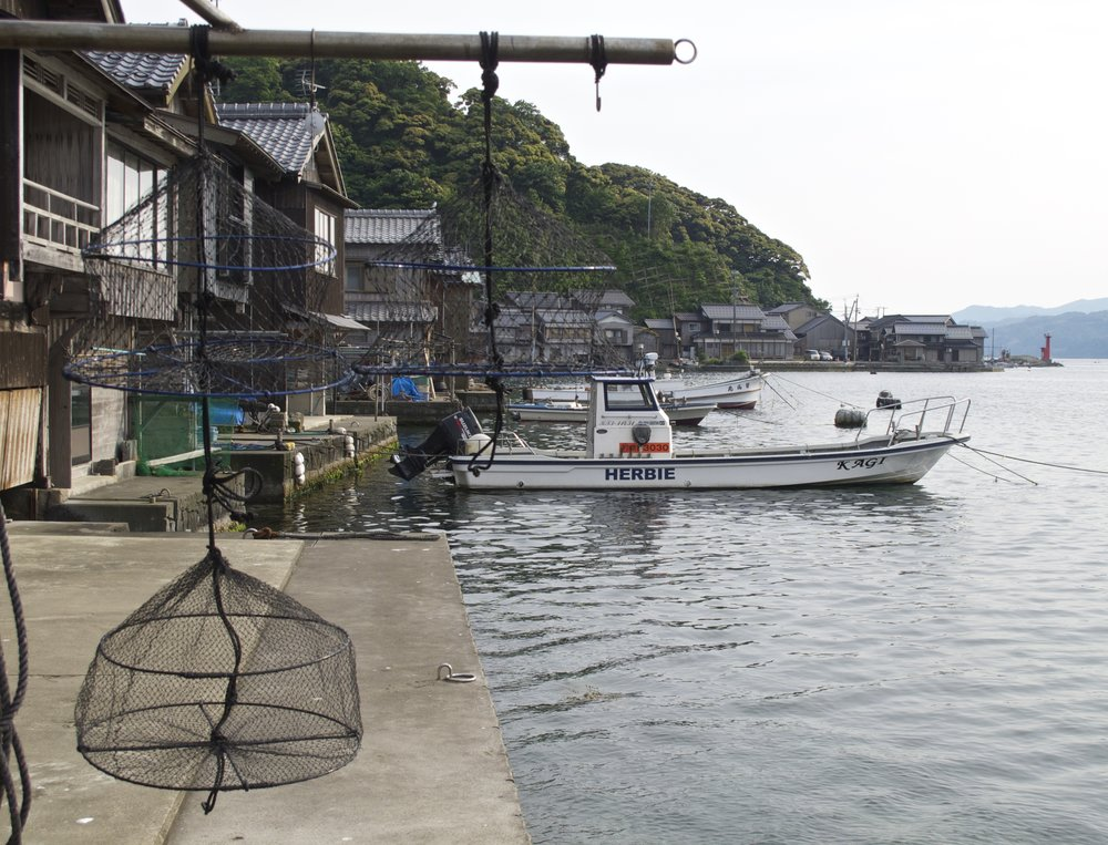 "Hanging in the left foreground is a small cage called a  mondori , which every household in Ine uses to catch fish directly from their  funaya . The skiff named ""Herbie"" moored in the background belongs to Kengo Kagi who runs a  funaya  guesthouse called Kaigya with his family."