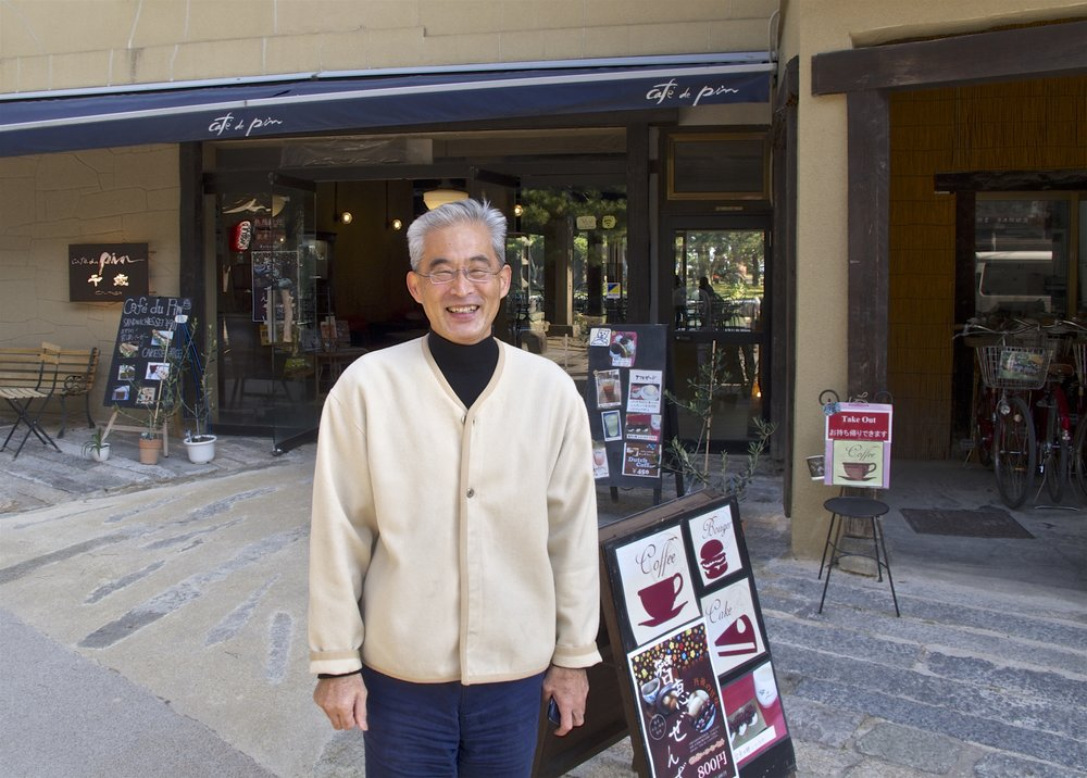 Proprietor of Wine and Inn Chitose, Hirotaka Yamazaki standing in front of Cafe du Pin. The inn consists of three buildings located on the main street of Amanohashidate. The main building is located a few doors down from the cafe and an annex is across the street.