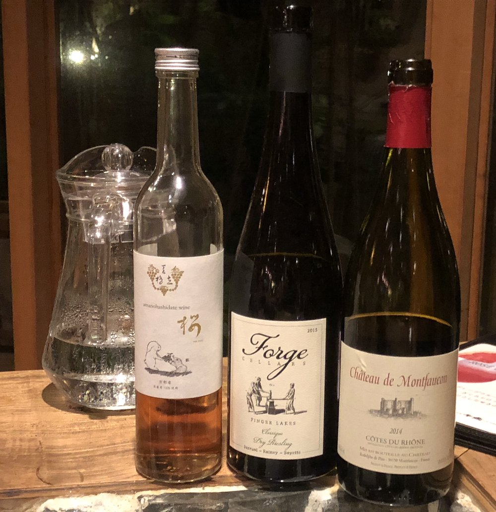 """On the left is a rose wine made by the Amanohashidate Wintery. In the middle, a bone dry """"Classique Dry Riesling"""" produced by Forge Cellars in upstate New York. One of the partners of Forge Cellars is Hirotaka's friend Louis Barruol of Chateau de Saint Cosme wines located in the Gigondas district of France. The Cotes du Rhone on the right is made by another friend, Rodolphe de Pins of Chateau de Montfaucon."""