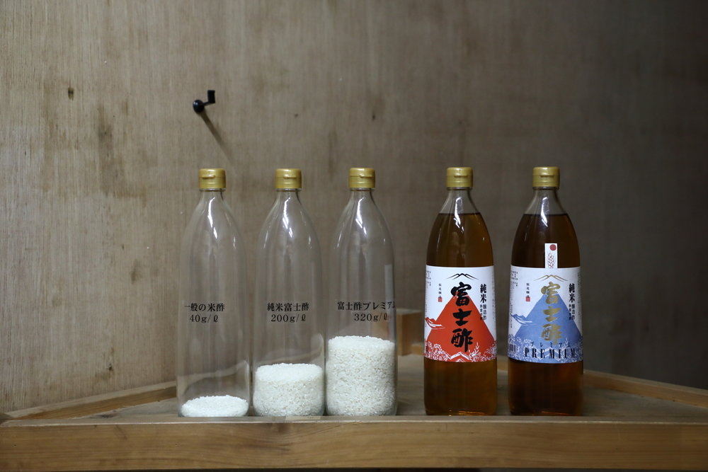 "A comparison of the rice content of commercially-made rice vinegar on the far left with Iio Jozo's ""Fujisu"" rice vinegars. The second bottle from the left is Iio Jozo's red label ""Junmai Fujisu"" rice vinegar (also pictured second from the right) and the center bottle is Iio Jozo's blue label ""Fujisu Premium"" rice vinegar (also pictured at the far right.) The much higher rice content in Iio Jozo's vinegars makes them mellower, richer, and healthier."