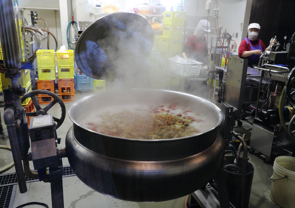 The vegetables are layered in large cauldrons, with the ones on the bottom being boiled and those on the top getting steamed.