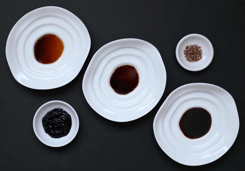"The different styles of artisanal Japanese soy sauces made to finish foods. At the top of the diagonal is Tanakaya's refined ""Premium"" first drip soy sauce. In the middle is Katakami's farmhouse soy sauce made with fruity green soy beans. At the bottom is Yamaroku's classic deep, rich ""Tsuru-bishio"" soy sauce, which is fermented and aged for four years. In the small dish in the upper right hand corner is Naogen's specialty crystalized soy sauce and in the bottom left hand corner Sawai's chunky soy sauce.  The large soy sauces dishes along the diagonal are among a variety of shapes being made to help people better use and appreciate artisanal Japanese soy sauce. Similar to ink stones used in calligraphy, the sloped design prevents people from pouring too much soy sauce by creating a small shallow pool at the center. The sloped sides help prevent using too much soy sauce when dipping and dragging food along them, while also enabling one to better see the soy sauce's true beautiful colors. Such dishes are also convenient chopstick rests."