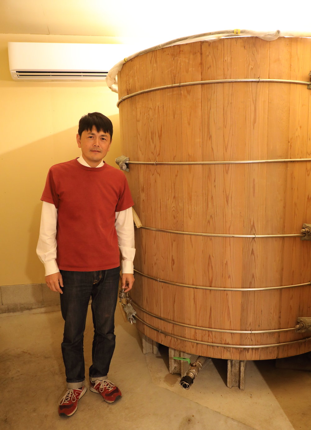 Daishi Torii standing next to one of the large  kioke  wooden barrels he uses to brew and lightly ferment his sauces.