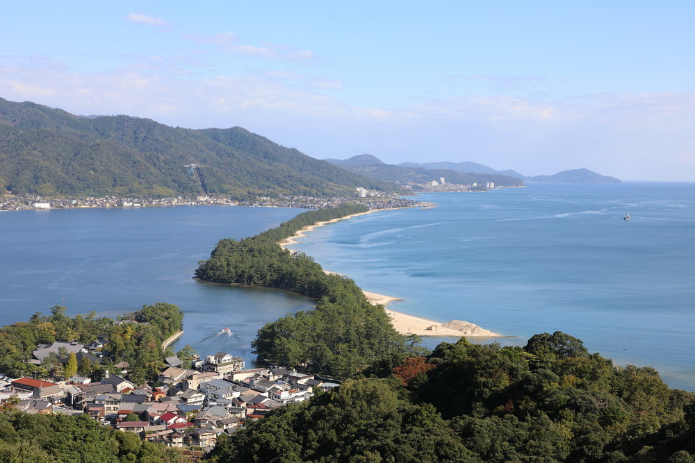 "The pine covered sandbar called ""Amanohashidate"". The small temple district also called Amanohashidate is shown in the left foreground."