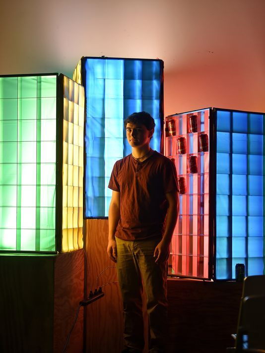 Zachary White, architect student at Mississippi State University. Standing in front of one of his light pieces. The piece is called 'pop light' & was inspired by Andy Warhol's pop art.
