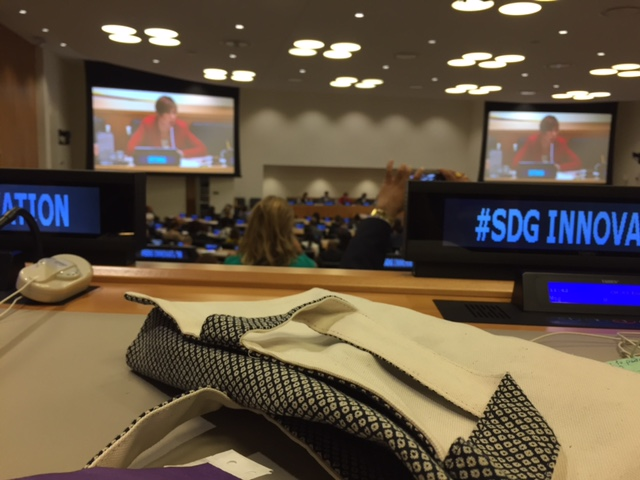 In the foreground an example of design innovation: The Aplat + Chef Melissa King Shibori Tote makes its debut at the UN. On the monitors, President Kersti Kaljulaid (Estonia).