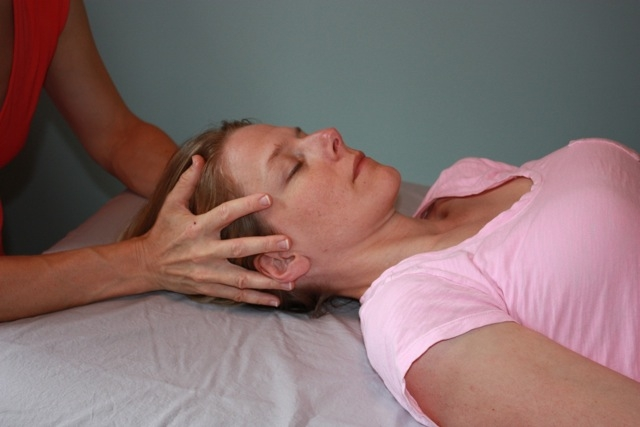 """Above, I'm using a """"vault"""" hold on the client. This hold originated with Dr. Sutherland, an Osteopath who gave rise to craniosacral therapy through his cranial concept within Osteopathy. It is a hold that allows the therapist to contact at once all the bones in the skull while staying present to the body as a biodynamic whole. It is an excellent hold to access the membranous system, including the dural membranes of the skull and spinal chord, and the brainstem which can be affected by blows to the head. Top Photo: Thoracic Inlet Hold, a great contact especially for calming a """"charged"""" sympathetic nervous system, the division of the autonomic nervous system that provides our """"fight or flight"""" response. It is also an effective hold to be present to the vast amount of anatomical structures running through the region of the neck."""