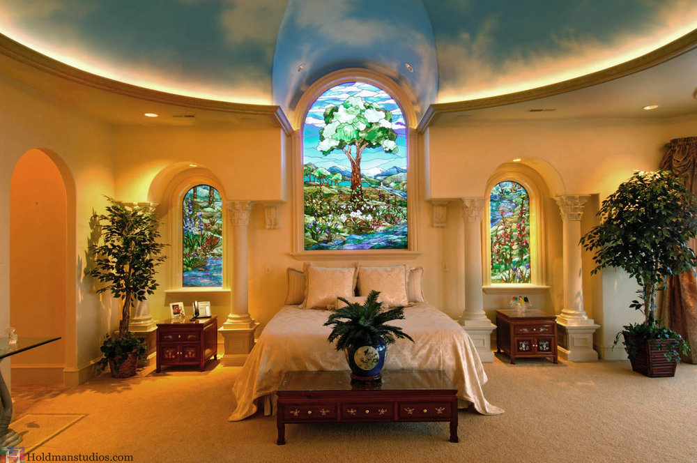 Stained Glass Bedroom windows with trees, river water, flowers, grass, mountains, and clouds in the sky. Created by artists under the direction of Tom Holdman at Holdman Studios.