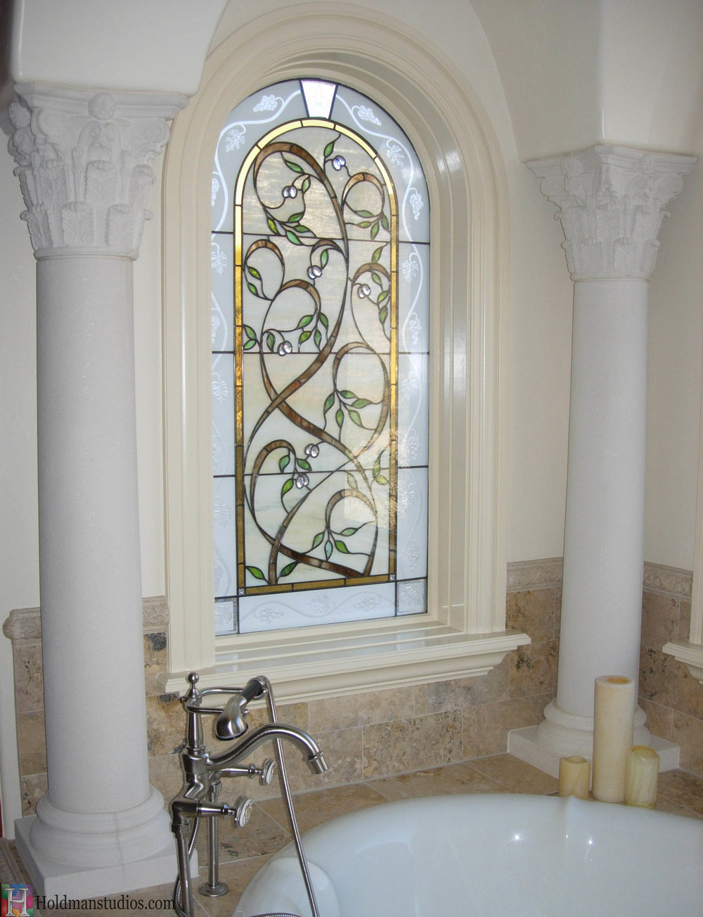 Stained glass bathroom window of vines, leaves, blossoms, and grapes. Created by artists under the direction of Tom Holdman at Holdman Studios.