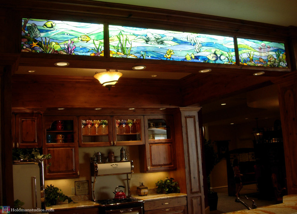 Stained glass kitchen window of sea water fish, turtles, plants, and shells. Created by artists under the direction of Tom Holdman at Holdman Studios.
