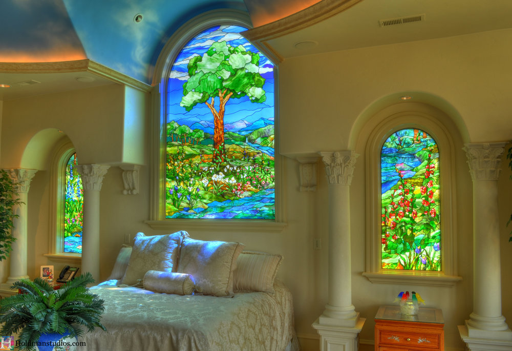 Side view of stained Glass Bedroom windows with trees, river water, flowers, grass, mountains, and clouds in the sky. Created by artists under the direction of Tom Holdman at Holdman Studios.