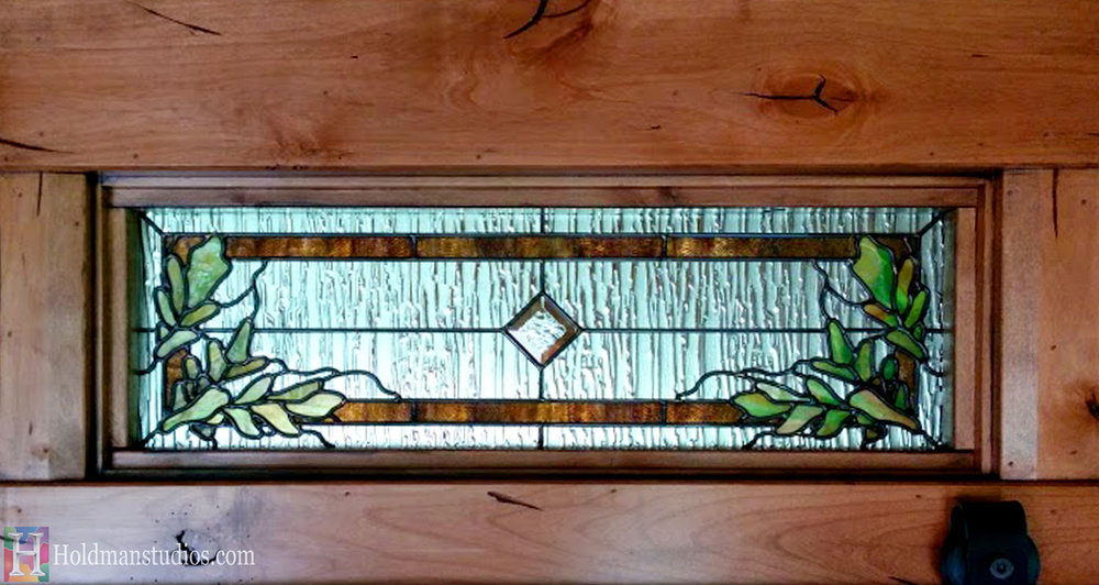 Stained glass door window of tulip flowers, and leaves. Stained glass transom window with leaves. Created by artists under the direction of Tom Holdman at Holdman Studios.