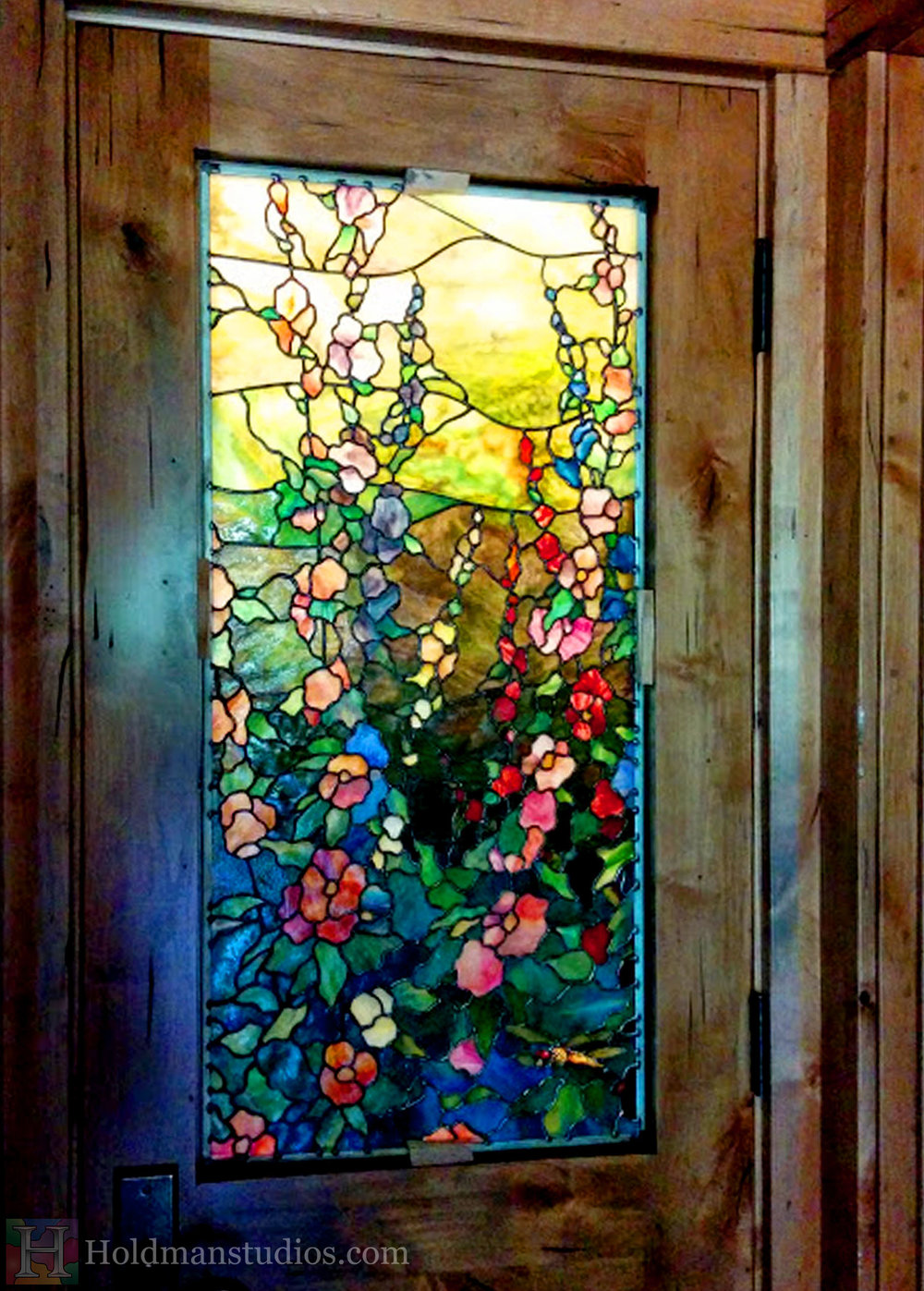 Close up of stained glass kitchen door window of flowers, leaves, rocks, and foliage. Created by artists under the direction of Tom Holdman at Holdman Studios