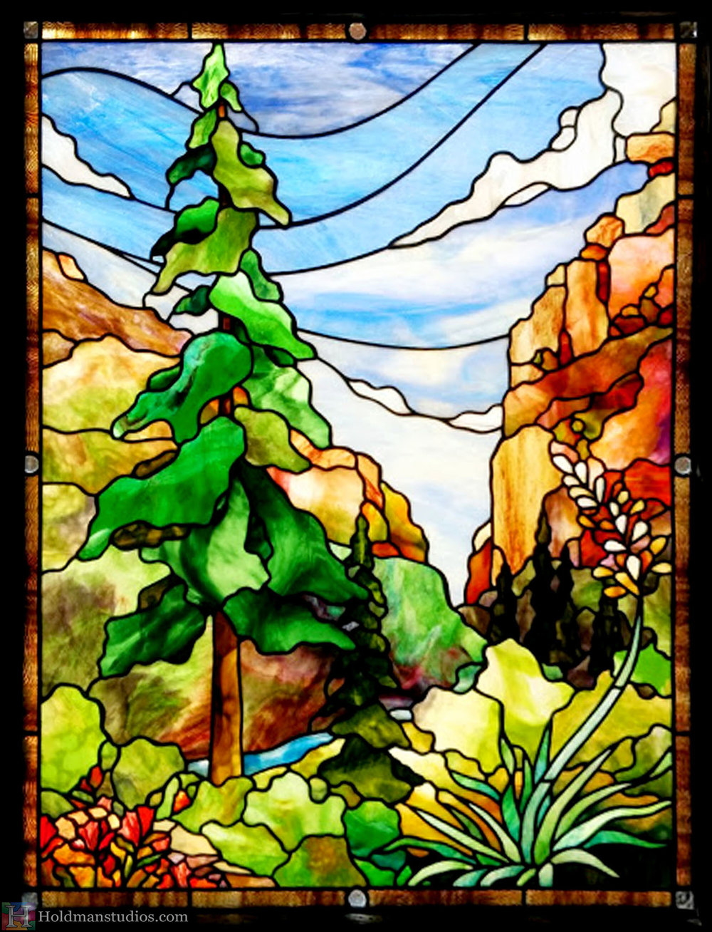 Stained glass front door window of the sky with clouds, mountains, pine trees, flowers, plants, and leaves. Created by artists under the direction of Tom Holdman at Holdman Studios.