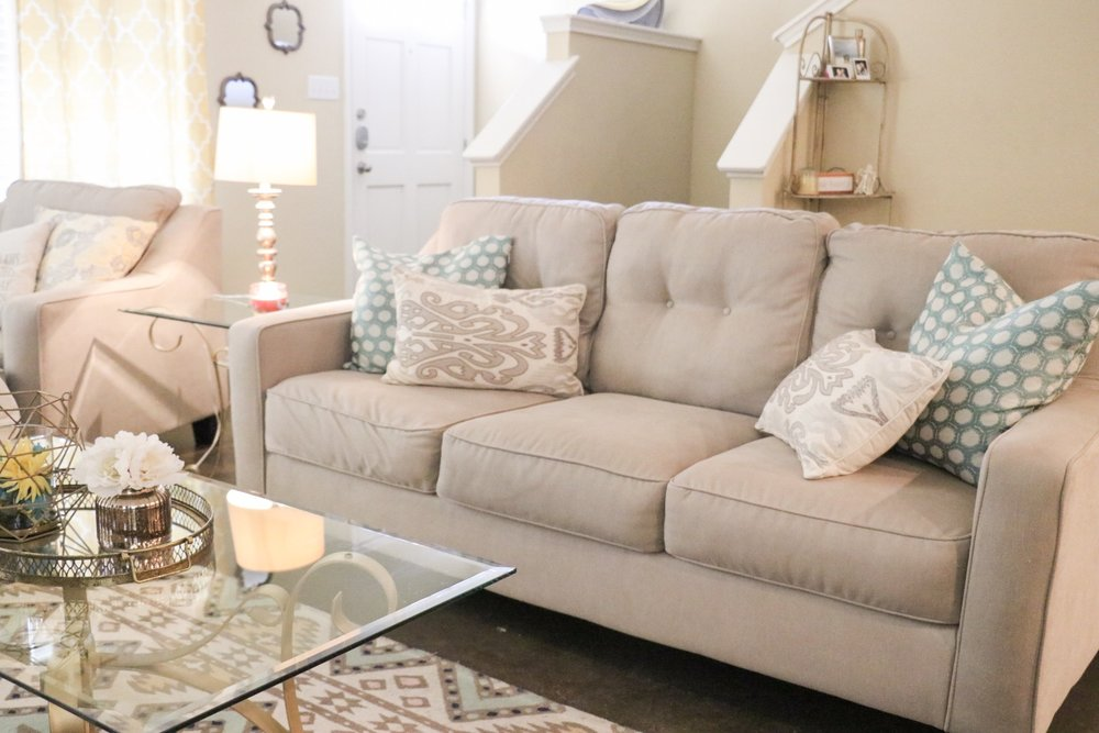 The moment I saw this couch, I fell in love. We had originally ordered different ones, but we had issues with the delivery and they showed up 4 hours early- before we were even in SA and then they gave us horrible customer service about it, so we ended up running around SA looking for couches! We got these at a furniture store near by in August. But  this one  is similar! The cream rectangular pillows were from the furniture store, and the aqua colored pillows are from Home Goods!