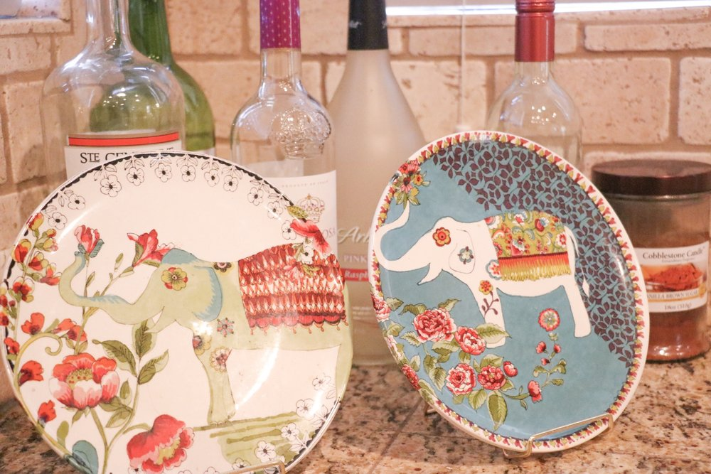 Behind our sink, we have 2 cute decorative plates from World Market placed on stands from Hobby Lobby. And then we currently have our empty wine bottles behind them (I plan on glittering them up soon)!