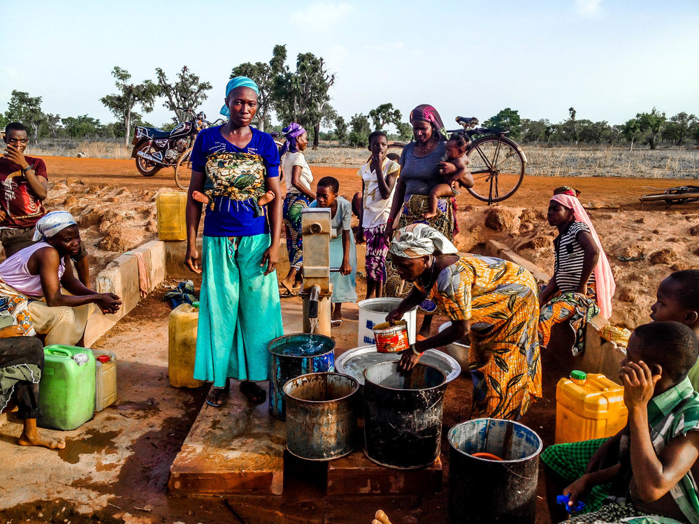 women and children of the kpduuli community futching water from the porn hole which is the only source to clean water.jpg