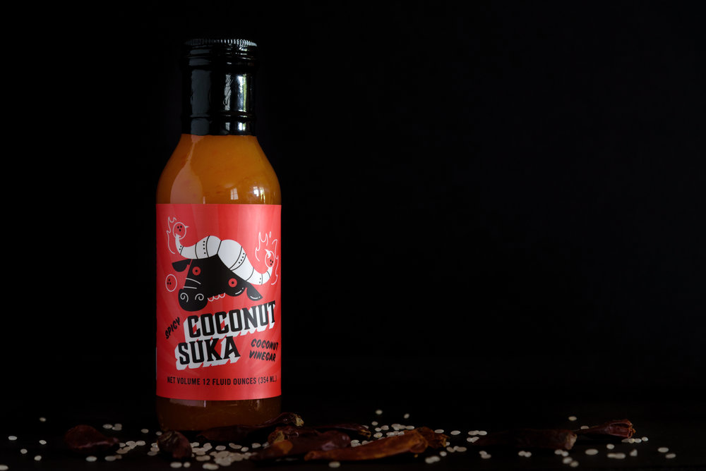 Coconut Suka - A spicy coconut vinegar.  We use fermented coconut water, and infuse Thai chilis, garlic, ginger, and fish sauce.  What results is a spicy, acidic, versatile ingredient for your kitchen.  Perfect for coleslaw dressing, smoked/pulled pork or chicken, a pickling vinegar for cukes, fish, or shrimp, finish braised collard greens or put it on your pizza, Suka is gluten-free and all natural.
