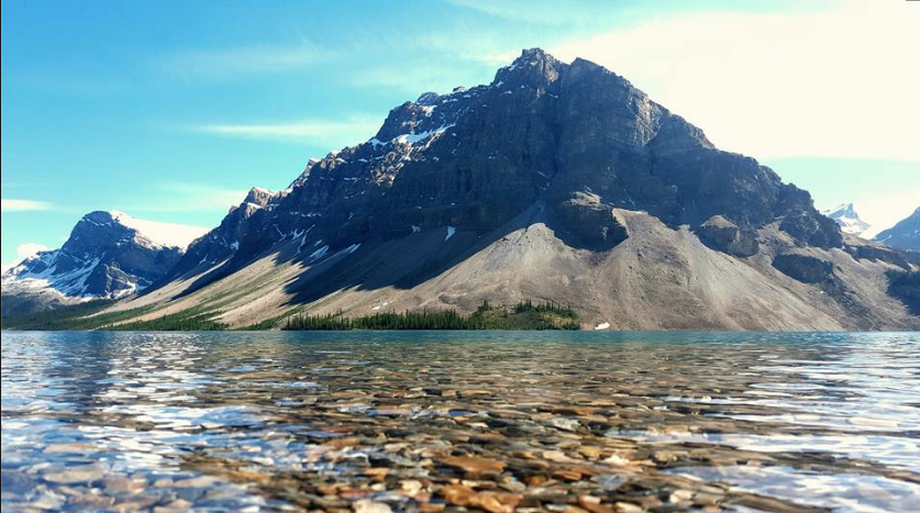 "Bow Lake  - Peacefully at rest at the foot of the prominent Crowfoot Mountain, the pristine waters of glacially fed Bow Lake can appear as turquoise as a tropical sea shore. The amalgamation of exceptional surrounding landmarks is the very reason Num-Ti-Jah founder Jimmy Simpson vowed to one day ""build a shack here."" And the rest... is History."