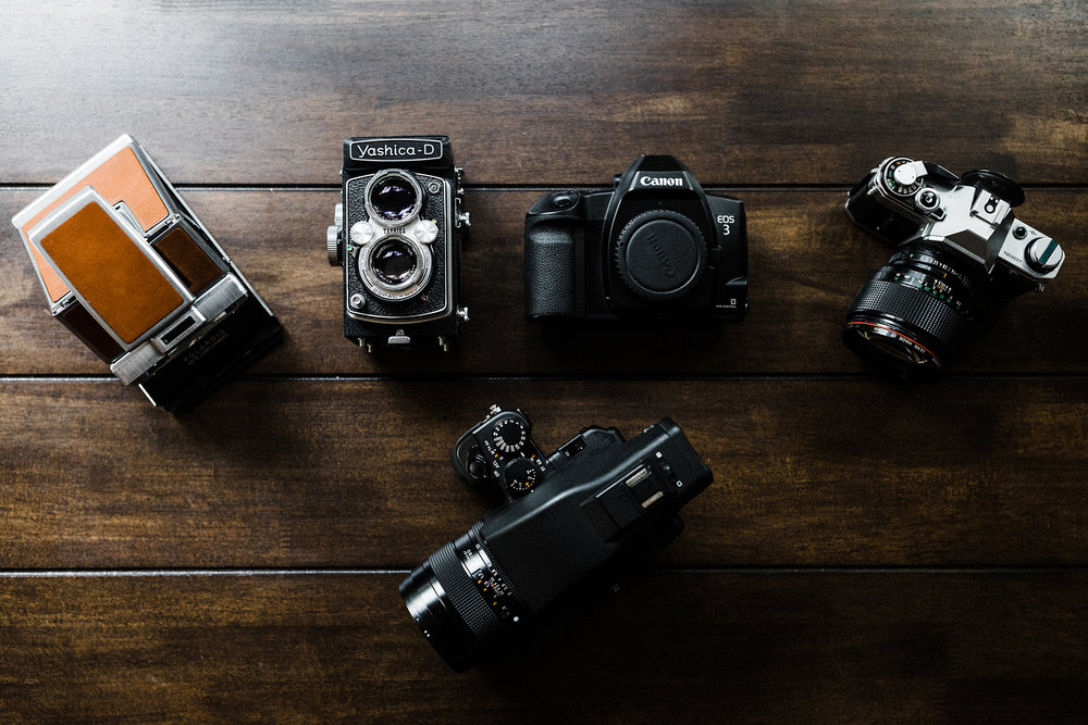 Left to right: Polaroid SX-70, Yashica-D TLR - 120mm, Canon EOS3 (allows you to use your DSLR Canon EF lenses), Canon AE-1 (very common and awesome manual 35mm camera), bottom is my pride & joy Contax 645 - 120mm camera.