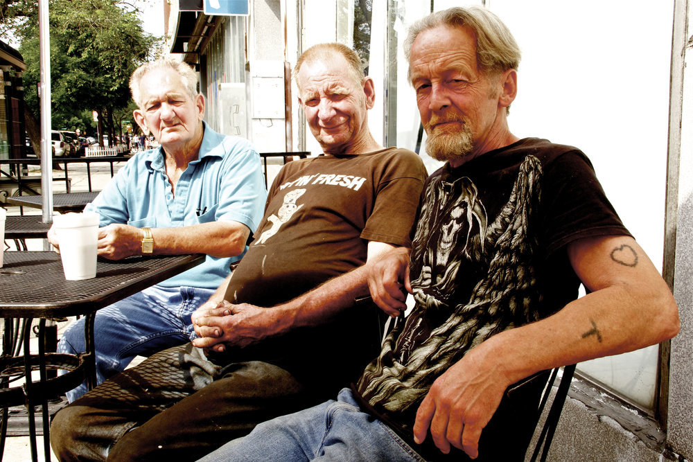 "The man in the middle told me that the man at the end wanted his picture taken.     ""Sounds like maybe you both want your picture taken?"" I suggested.     ""Well, okay,"" the man in the middle conceded and scooted his chair over.      The man in front had been standing behind me on the sidewalk.     ""What's happening?"" he asked. ""What's happening here?""     ""Taking their photo,"" I told him, and he hopped the fence and sat down in front."