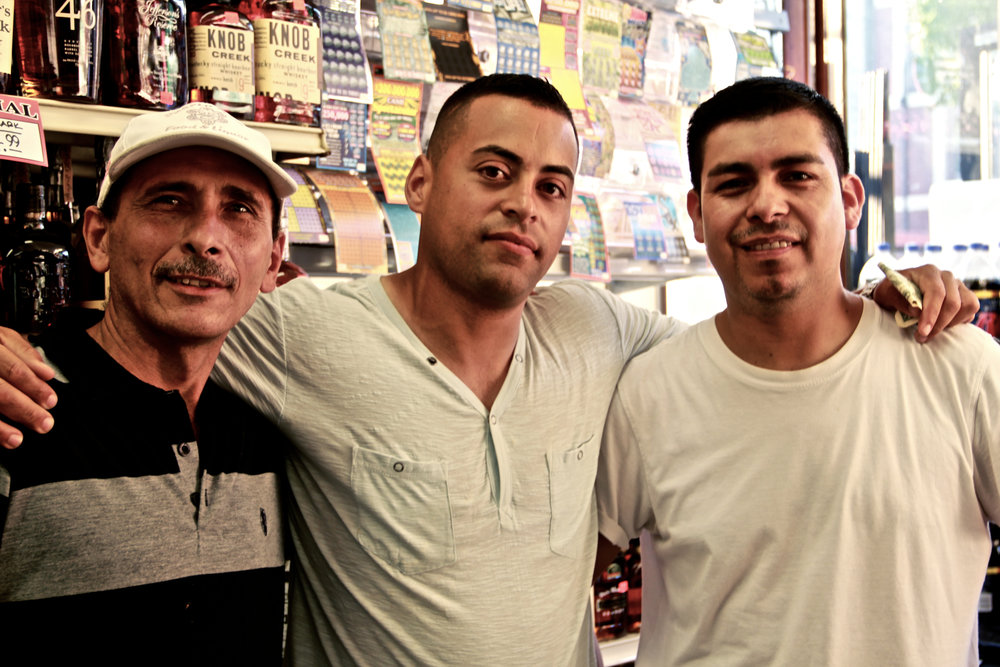"I went into a corner store with the camera around my neck when the man in the middle first made a comment. I told him I'd be happy to take a picture, but it took some convincing from his co-worker before he really went for it. At the last minute the guy in the hat was invited in.      ""You tell us when,"" the first man said as I adjusted some camera settings.      ""Right,"" said his co-worker. ""One, two, three, 'fuck.'"""