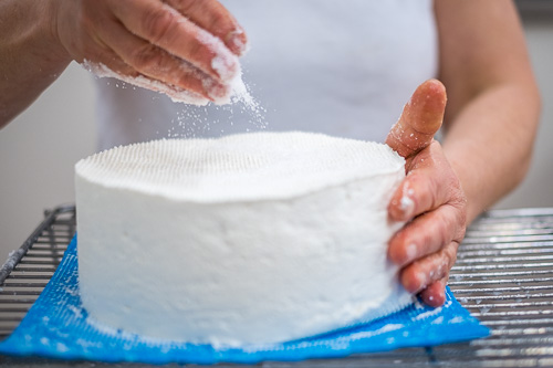 Handgezouten - Het handmatig inzouten van de kazen vergt ervaring en oog voor het detail. Onze kazen hebben geen vast gewicht en de zoutdosis moet dan ook telkens per kaas bepaald worden. Nooit te veel, nooit te weinig. Deze methode verhoogt de perifere concentratie van zout (meer dan bij een pekelbad) en vertraagt de penetratie van het zout.