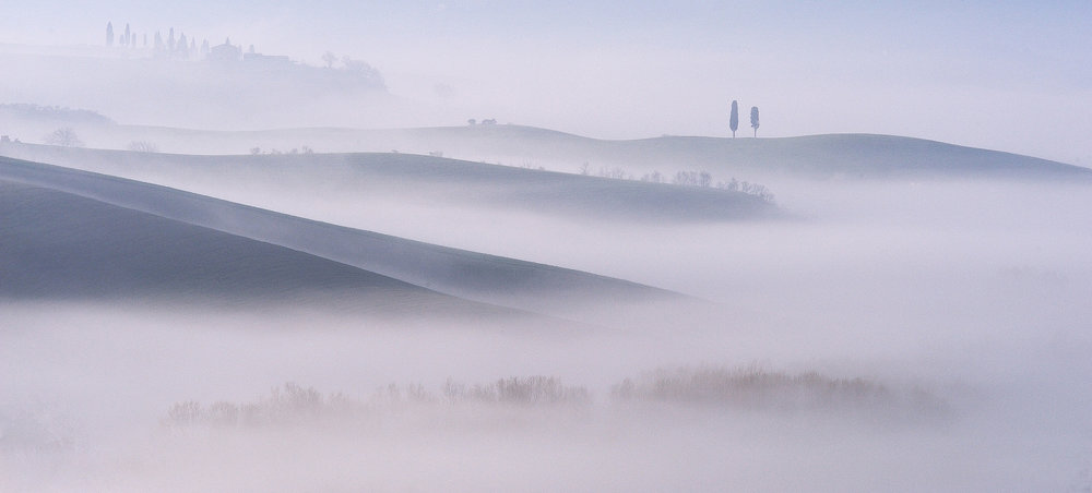 Two The rolling hills of Val d'Orcia in mist at dawn