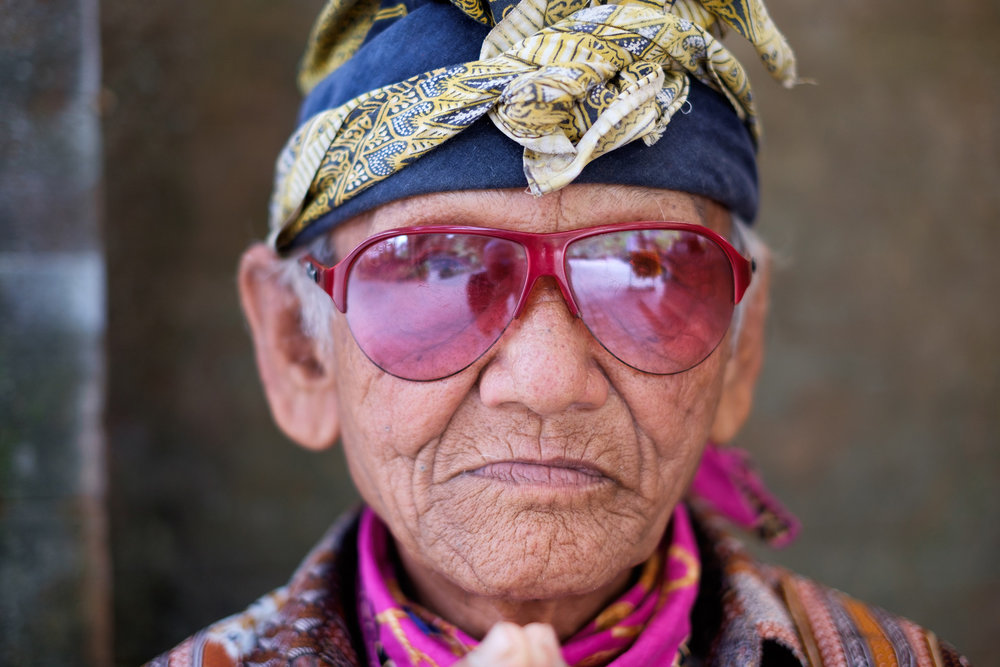 Red Sunglasses   One of my favourite portraits from Indonesia, this old man was sitting at a counter where they gave people sarongs to wear inside the temple of Tirta Empul in Bali. I spotted him and his incredibly colourful clothes as I was leaving and asked if I could take his photo.