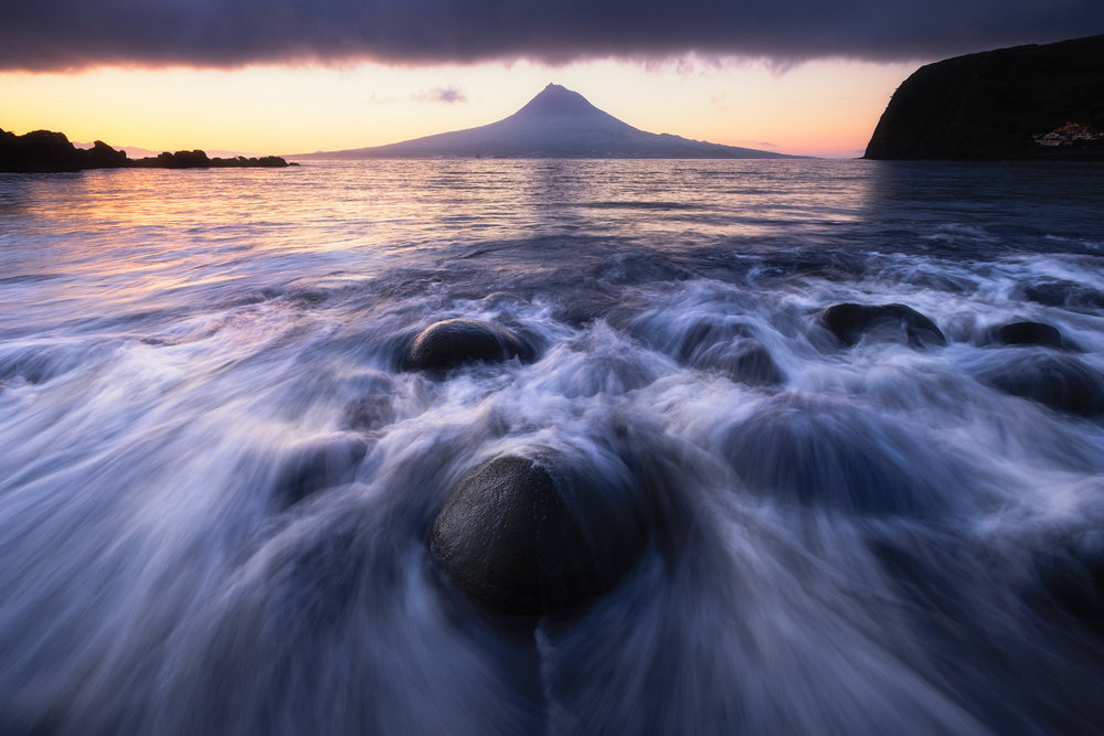 Almoxarife Dawn   Waves wash onto the black sand beach of Almoxarife on the island of Faial in the Azores. Across the narrow channel the mountain and island of Pico rise above the ocean