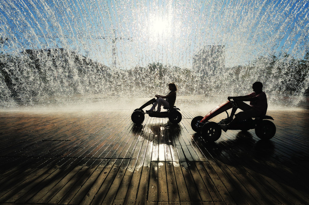 Summer in the City Two kids ride gokarts beneatht the waterfalls at the end of the day in Parque das Nações
