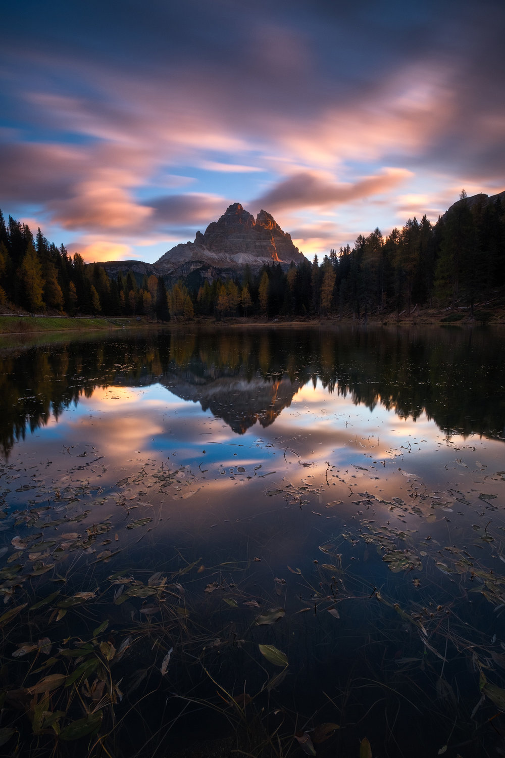 Tre Cime Sunrise The sun's first rays paint the peaks of Tre Cime di Lavaredo reflected in the still waters of Lago Antorno in the Dolomite mountains.