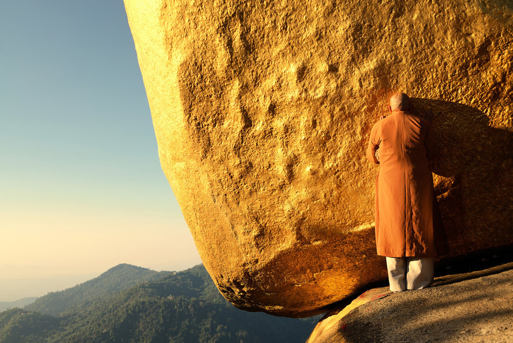 Golden Rock    A monk prays at Golden Rock as the sun rises on top of Mount Kyaiktiyo.  One of the most sacred Buddhist pilgrimage sites in Burma, people travel from all over the country to touch, apply gold leaf and pray at Golden Rock, a huge boulder  balanced precariously on the edge of a cliff.  Legend has it that the rock is held in place by a single strand of Buddhas hair.  We travelled here from Yangon, spent the night at the temple site, and woke up before dawn with all the other pilgrims to see the sun come up over the mountain.  The atmosphere was full of incense as thousands of people gathered around the rock.  An unforgettable experience.
