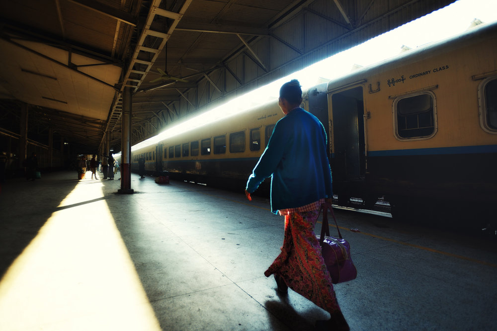 Yangon Train Station   A woman hurries along the platform just after dawn at Yangon central train station