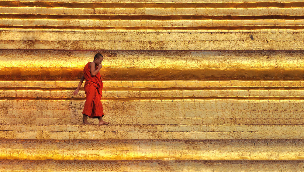 Red and Gold   A monk walks along the edge of the stupa at as the day's last light illuminates the golden Shwedagon Pagoda in Yangon. On our first evening in Burma we went over to Shwedagon and found it full of thousands of local people come to pray, burn incense and just soak up the atmosphere in Burma's most religious location. Legand has it that Shwedagon Pagoda has existed in one form or another for 2600 years and it's impossible to go there and not be impressed by the sheer size and of the 100 meter high gold covered stupa.
