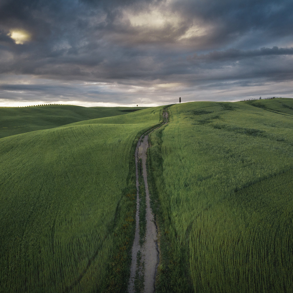 A drone image of the rolling hills of Tuscany at sunset
