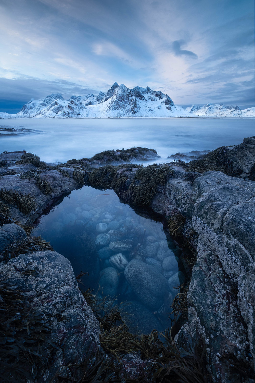 Vareid   Low tide reveals rock pools on a cloudy sunrise in Vareid, the Lofoten Islands