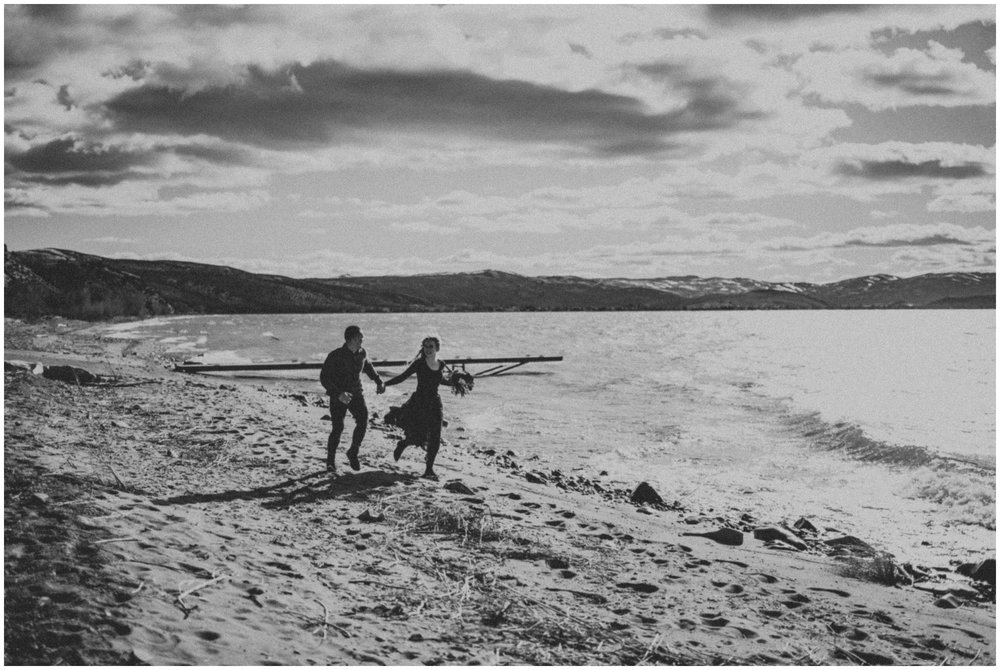 Moody black and white of a couple running on the beach  | Wedding Photographer Bear Lake Utah www.riversandroadsphotography.com