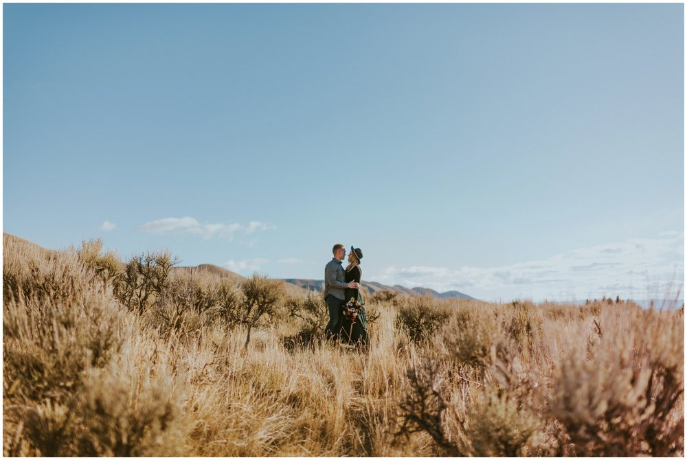 Couple facing each other in the desert in Utah with mountains in the background | Wedding Photographer Bear Lake Utah www.riversandroadsphotography.com