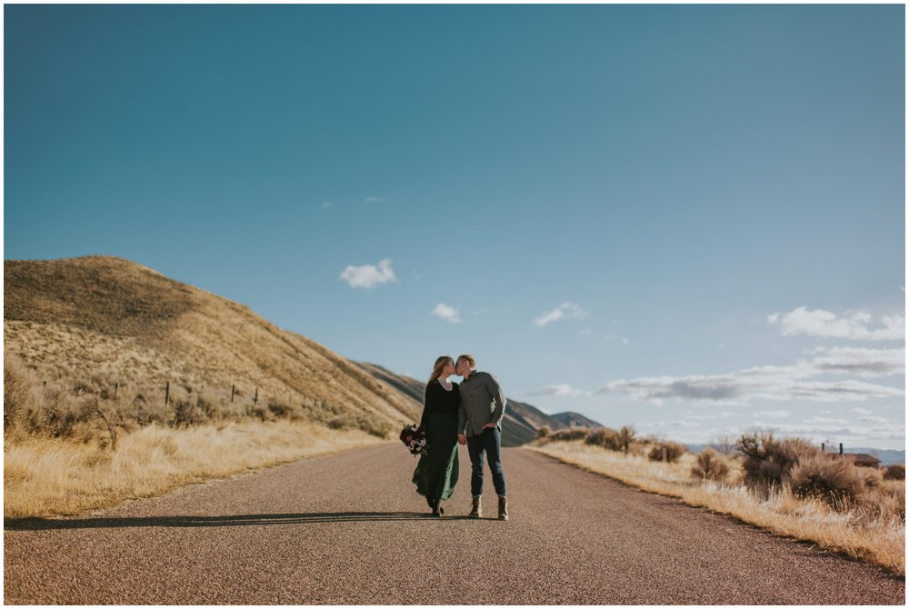 Couple kissing in the middle of the road out west with the blue sky and mountains in the background  | Wedding Photographer Bear Lake Utah www.riversandroadsphotography.com