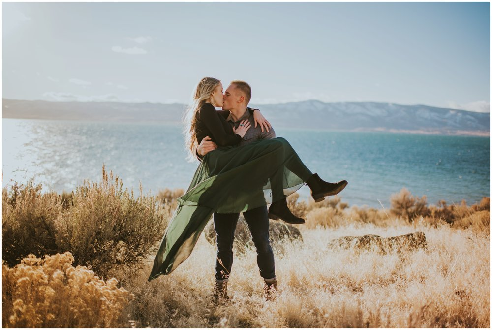 Guy picking up girl and kissing her in a field at Bear Lake with blue mountains in the background  | Wedding Photographer Bear Lake Utah www.riversandroadsphotography.com