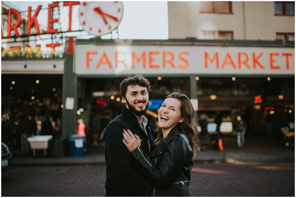 Couple laughing in front of Pike Place Market in Seattle Washington | Engagement Photographer www.riversandroadsphotography.com
